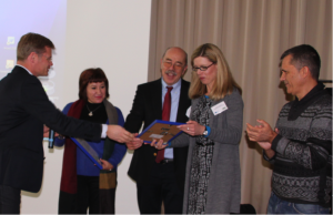 Der Vertreter des Hessischen Kultusministeriums überreicht die Urkunde